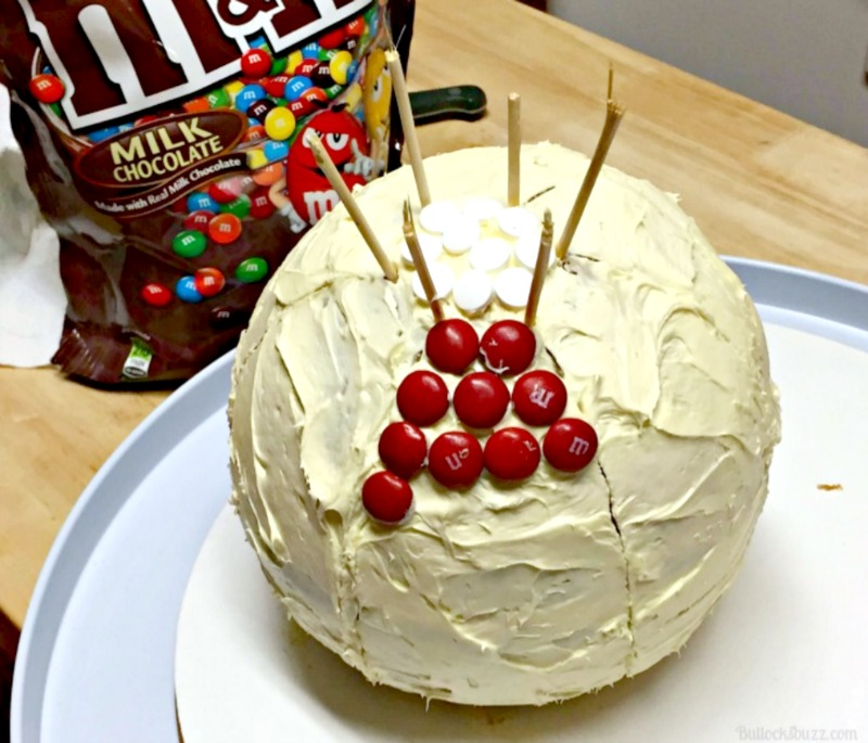 Beach Ball Cake with M&Ms begin adding M&Ms