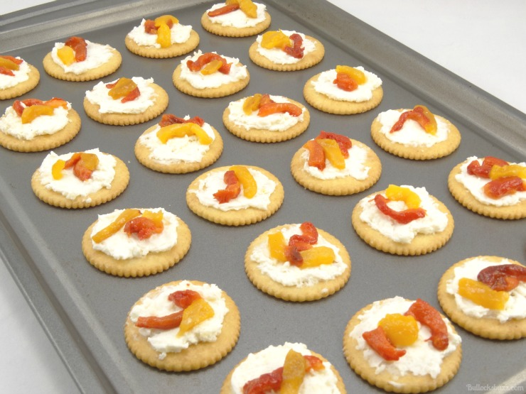 Roasted Pepper Cheese Bites and Holiday Party Planning Tips put crackers on baking sheet top with peppers