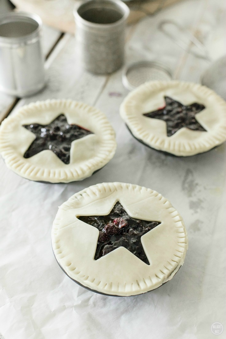 mini blueberry pies add the lids and crimp around edges with a fork