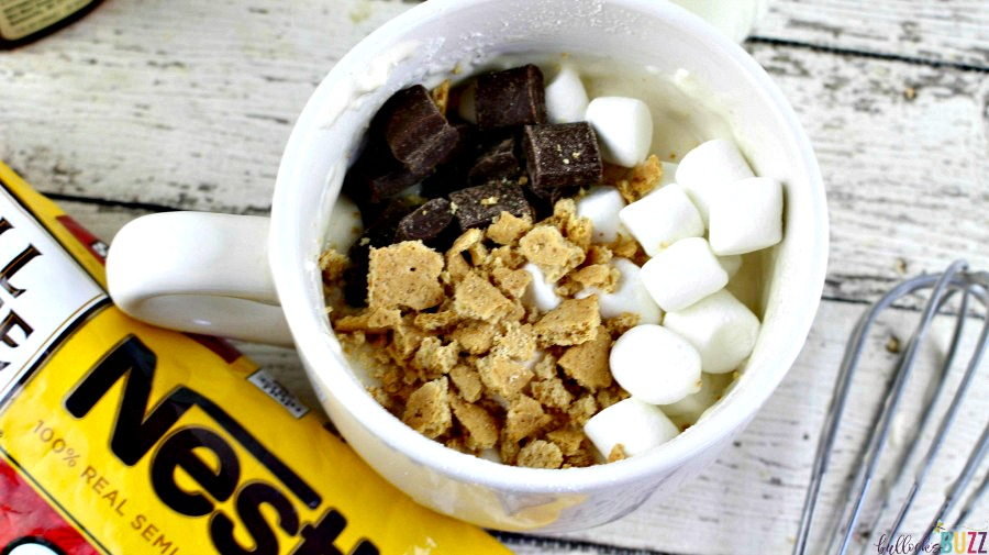 Add marshmallow, chocolate and crackers stirring to combine for a S'mores Mug Cake