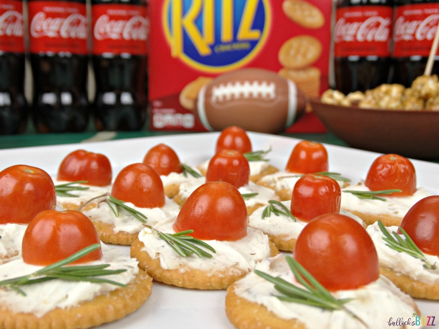 Top each cracker with the herbed cream cheese and a slice of tomato and rosemary to complete this game day recipe for Rosemary, Tomato & Herbed Cream Cheese Bites