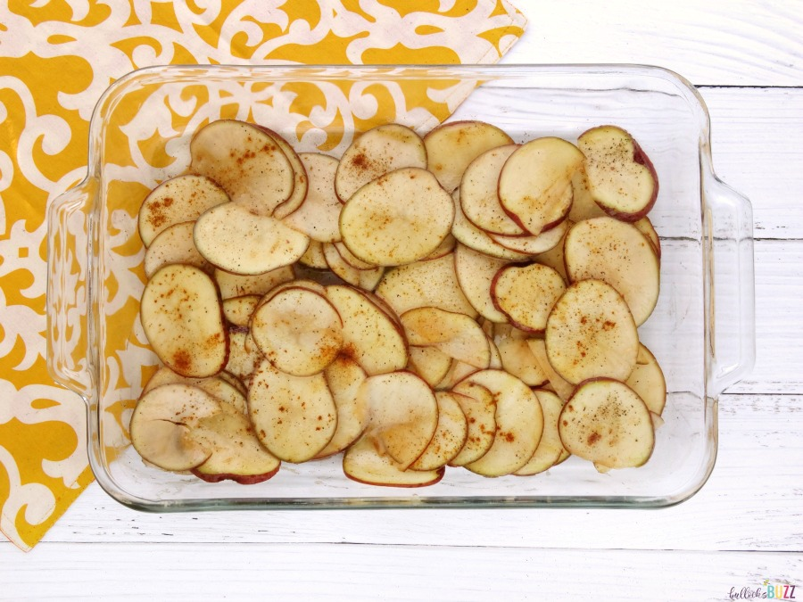 Thinly sliced and seasoned potatoes in baking dish to make oven roasted red potatoes