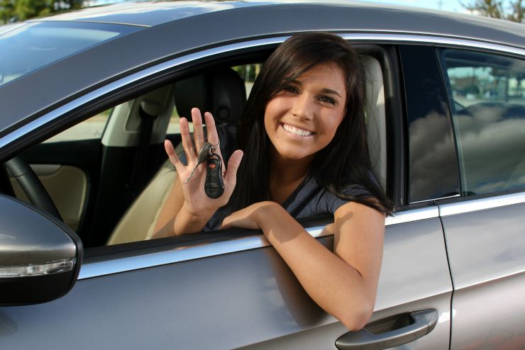 happy teenager in car holding keys