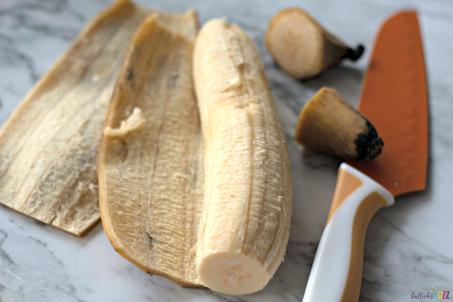 cut ends off then slice down middle and unwrap plantain to make Sweet Fried Plantains