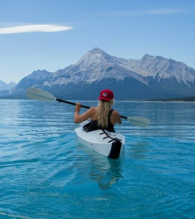 kayaking in lake surrounded by mountains