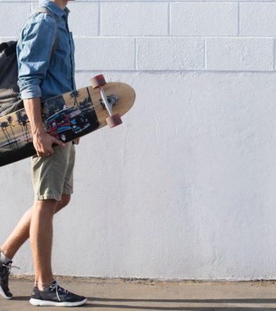 man carrying a longboard skateboard