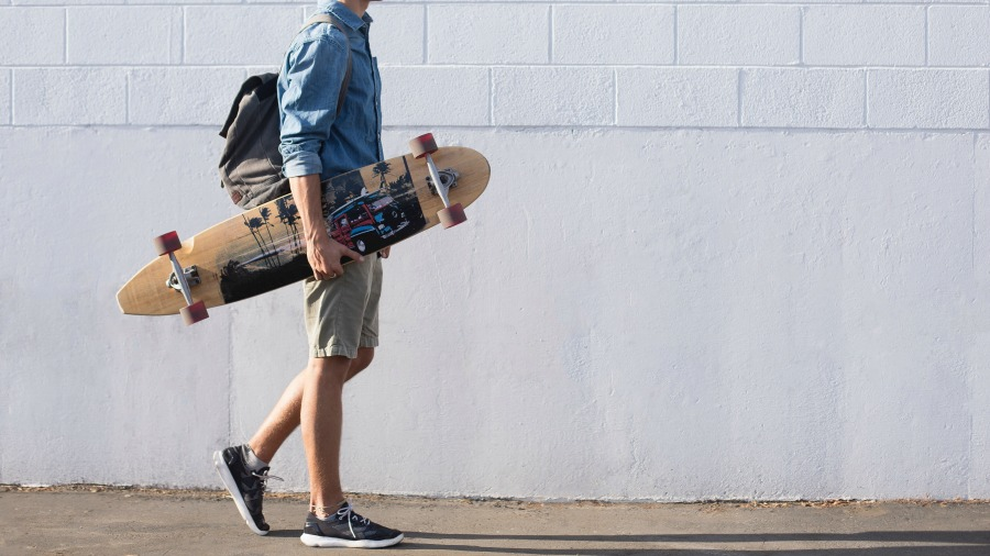 man carrying a longboard after deciding which longboard youo should buy