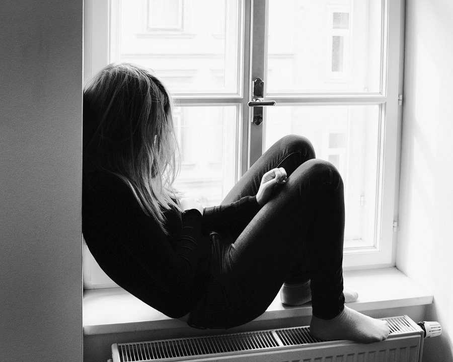 girl sitting in window suffering from teen depression