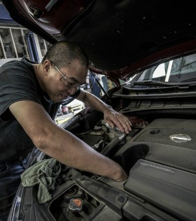 car mechanic working on car with Ultimate Car Maintenance Checklist