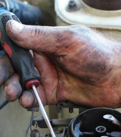car mechanic working on reasons your check engine light is on