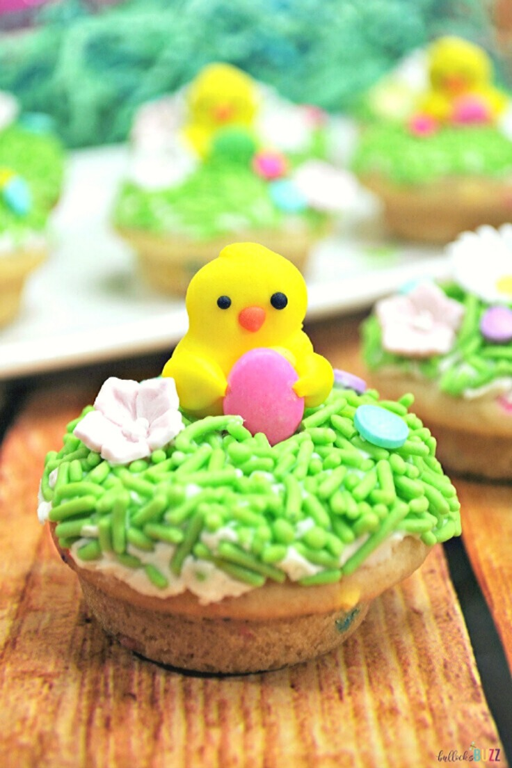 A delicious Easter Sugar Cookie Cup recipe that is decorated with candy grass and an adorable spring Chick and candy Easter eggs.These Easter Cookie Cups are SO simple and make the perfect Easter dessert! Get the recipe on the blog at Bullock;s Buzz. #Easter #Easterrecipes #cookiecups