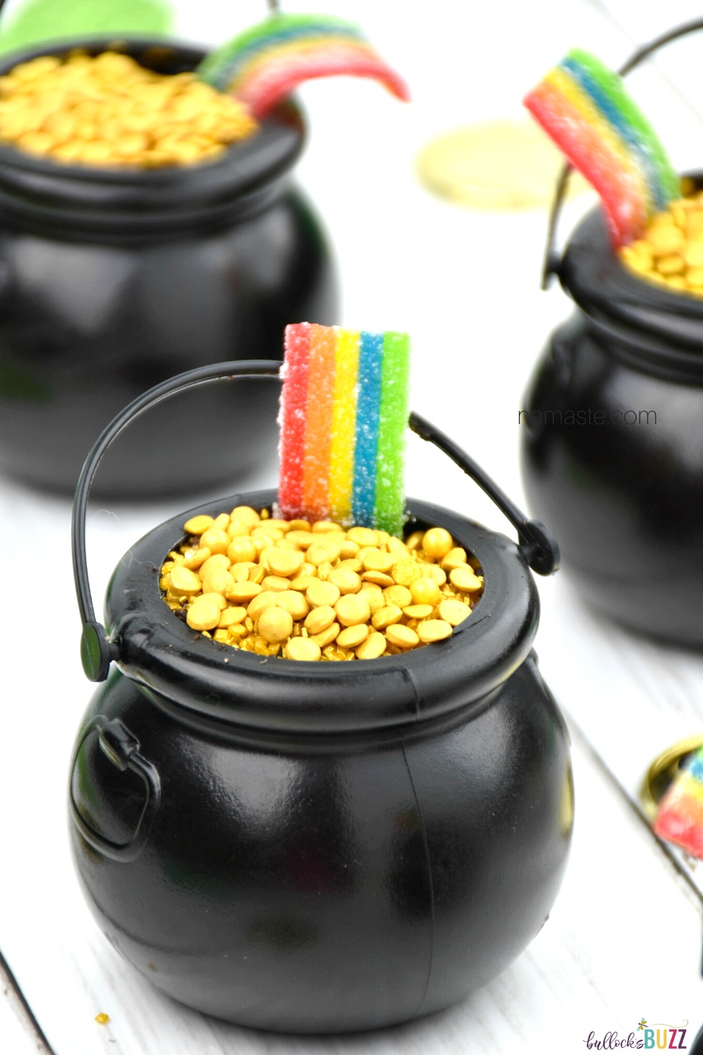 Layers of rich, chocolatey cookies and creamy chocolate pudding, topped with gold sprinkles, and sour rainbow candy make these St. Patrick's Day Pot of Gold Dirt Cups taste as good as they look! #recipes #StPatricksDay #bullocksbuzz