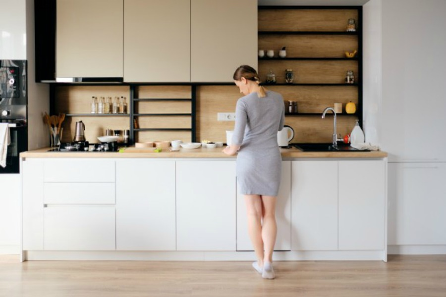 woman standing in front of kitchen cabinets