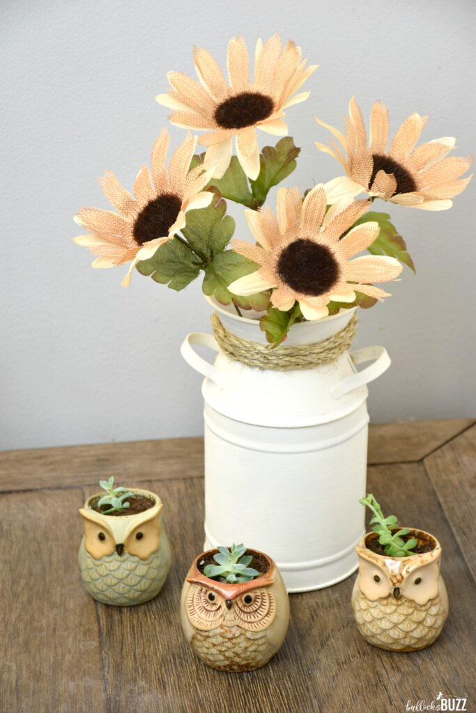 You can make this simple DIY Milk Can Vase Centerpiece in minutes using nothing more than a galvanized milk can, some paint, a bit of rope, and a few faux flowers.