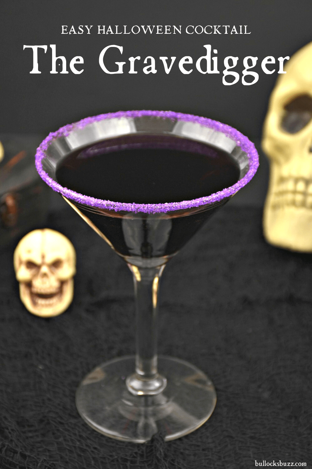 dark purple Halloween Cocoktail in cocktail glass with purple sugar rim