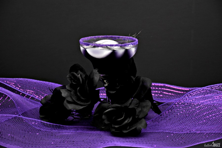 Halloween cocktail in glass surrounded by black roses