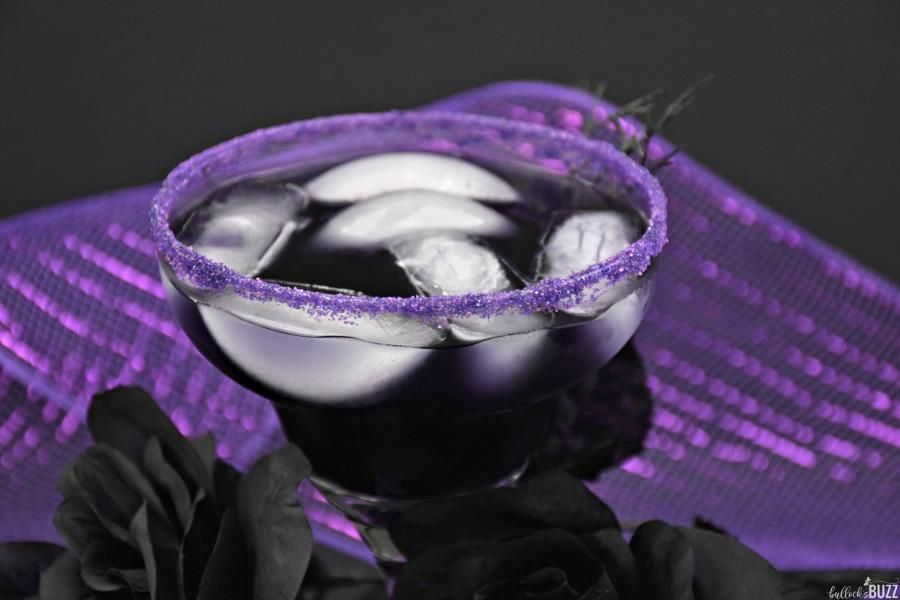 purple cocktail with purple sanding sugar on rim