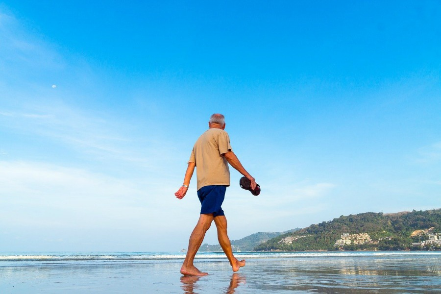 exercising, like this man on the beach, is one of the best health tips for seniors