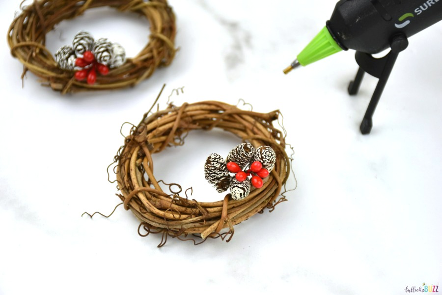 use hot glue to attach pinecone and berry picks to wreath