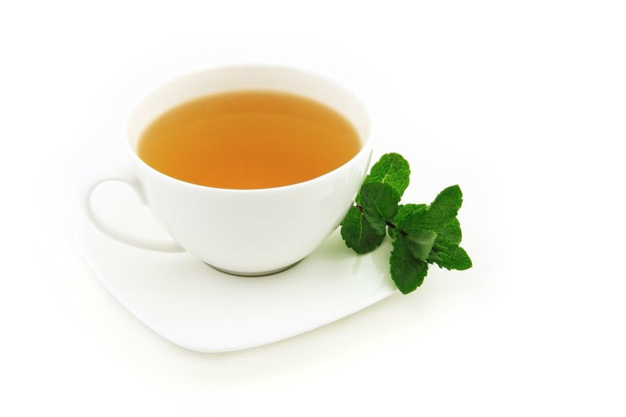 white cup of green tea with fresh mint leaves on the side