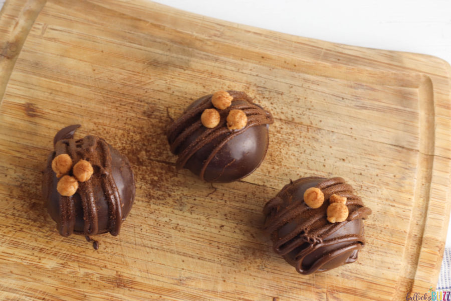 decorate the finished Caramel Mocha Coffee Bombs with a drizzle of chocolate, a caramel bit and sprinkle of espresso powder