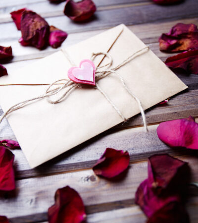 love letter with small pink heart surrounded by rose petals