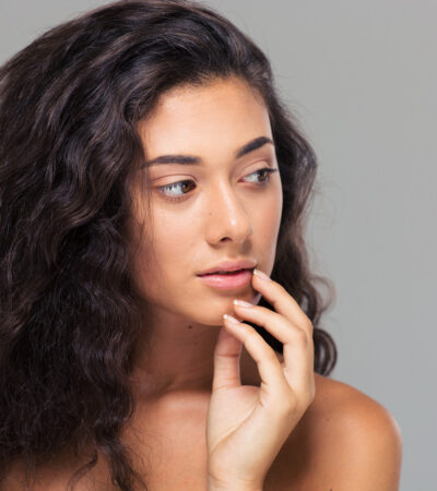Beauty portrait of a lovely woman with fresh skin from perfecting your skincare routine looking away over gray background