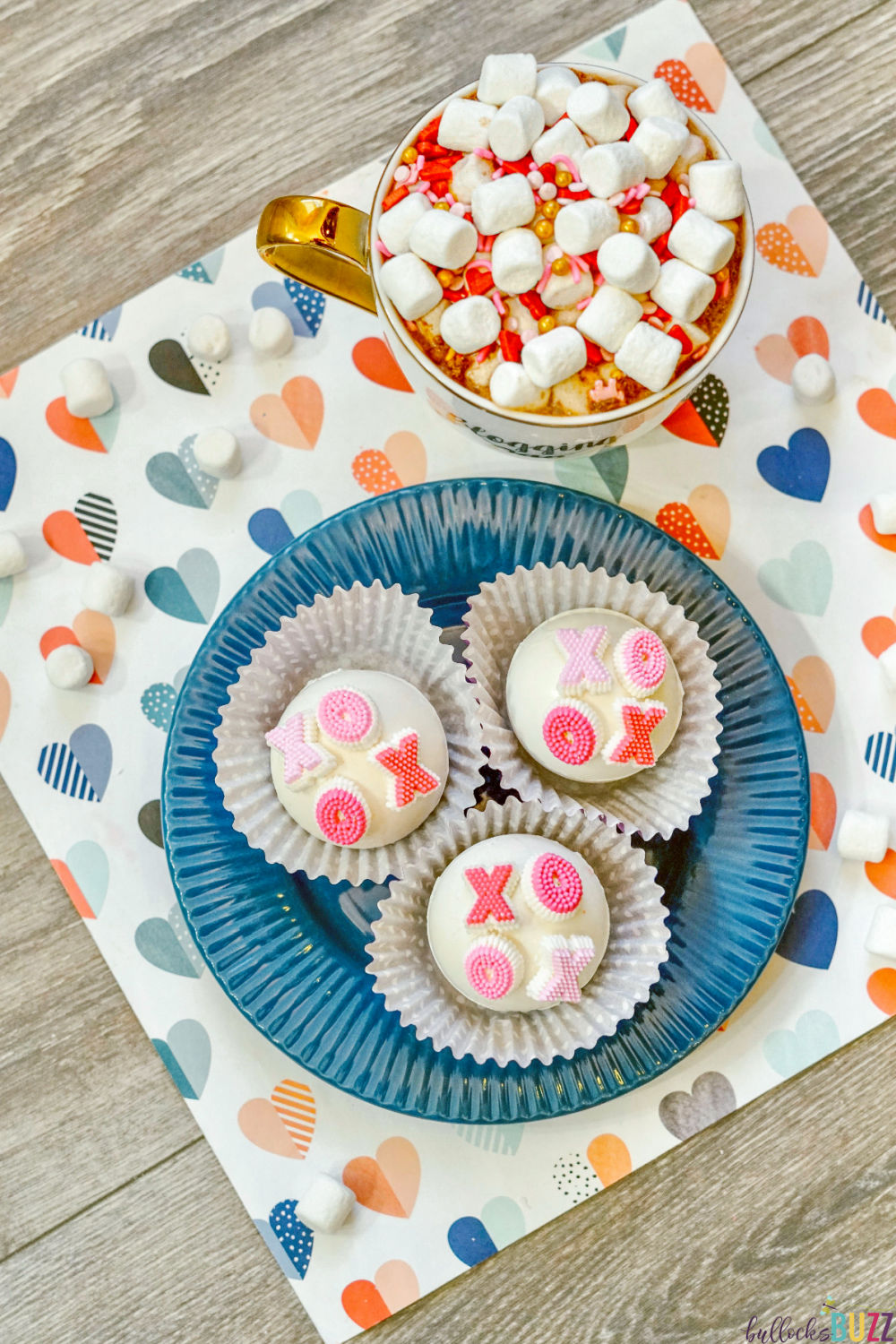 Homemade white chocolate spheres are filled with hot cocoa mix, sprinkles, and mini marshmallows, then decorated with XOXO candies for a delicious hot cocoa drink you will love! These XOXO Valentine's hot cocoa bombs are, well, the bomb!