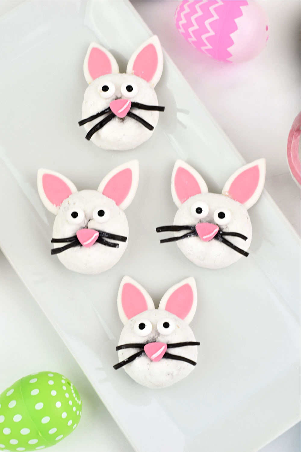 Delicious white powdered donuts are topped with adorable bunny ears and faces in this fun no-bake Easter dessert recipe that doubles as Easter dessert table decor.