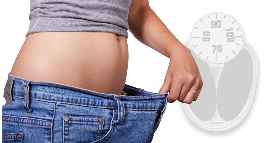 woman in too big jeans and the benefits of losing weight