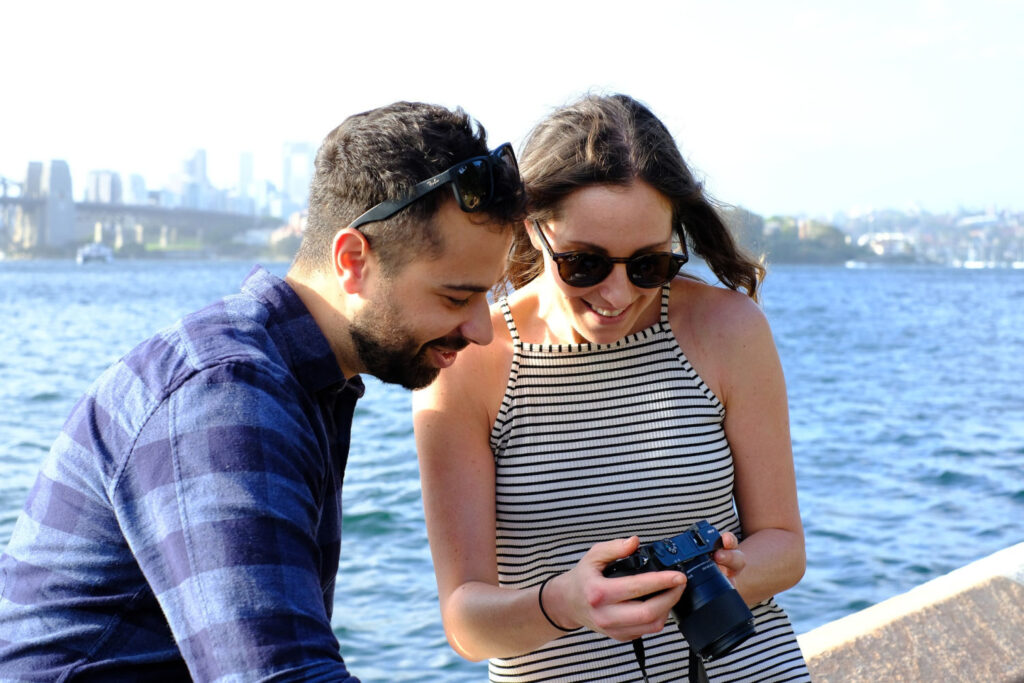 couple by the water looking at images on camera