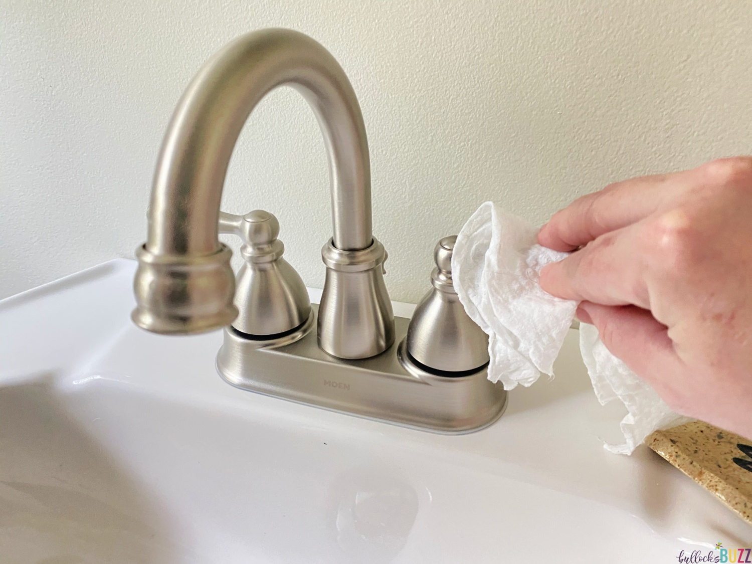 cleaning faucet with Arm and Hammer Essentials Disinfecting Wipes as part of weekly cleaning schedule