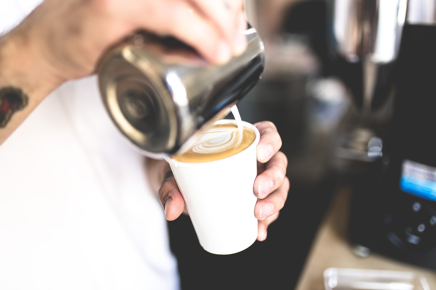pouring milk to make latte art on top of the most popular espresso drinks