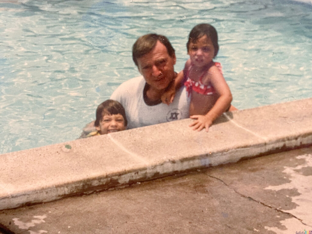 An old picture of my dad, sister and me swimming in a pool when we were little kids.