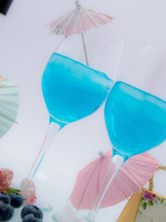 two blue cocktails on a tray
