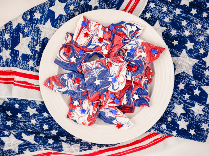 red, white and blue candy bark on a white plate