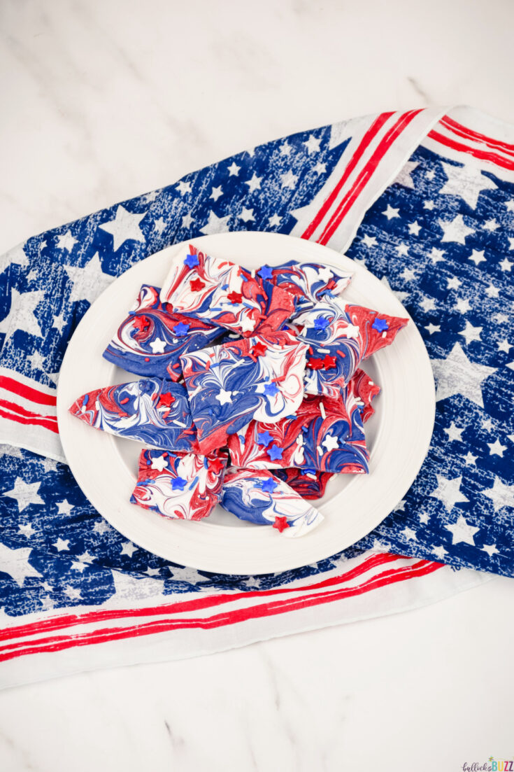 Making this red, white, and blue candy bark is as easy as melting the candy melts, swirling them together, and then adding the sprinkles. Then you let it sit until it's ready to eat. #4thofJuly #candybark #candy #recipe #candyrecipe