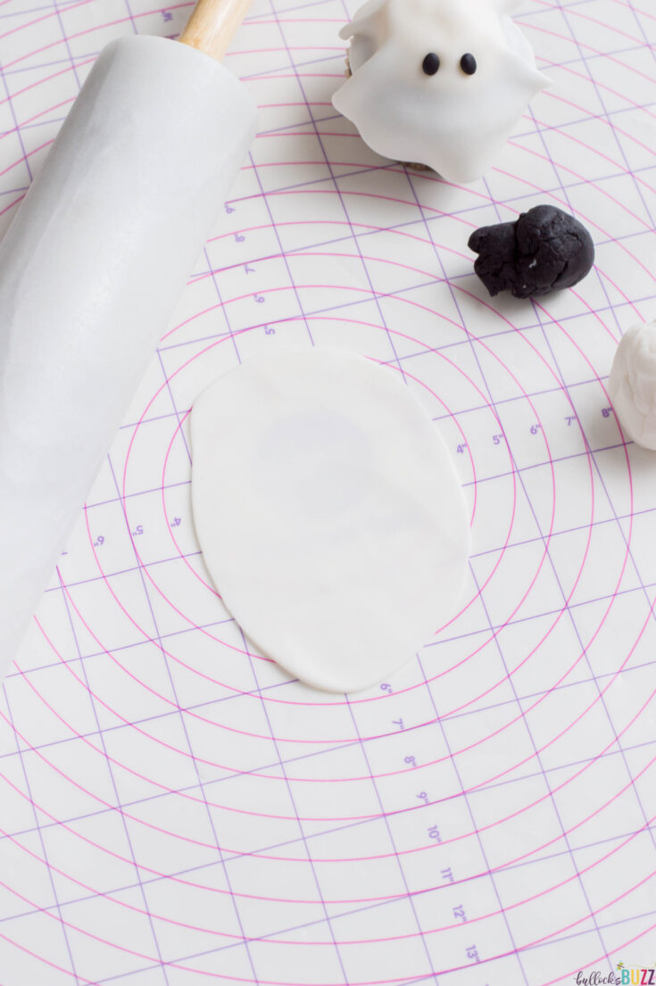 roll out fondant circles to form ghosts for Halloween ghost cupcakes